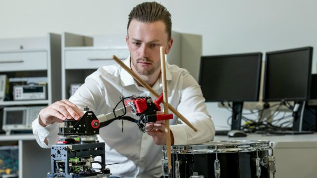 Man sits adjusting dials on a mechatronic robot system and drum.