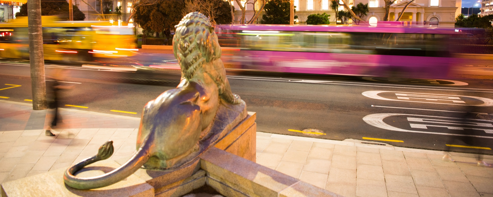 Looking from behind a lion statue across the road at dusk, with the Old Government Buildings in the background