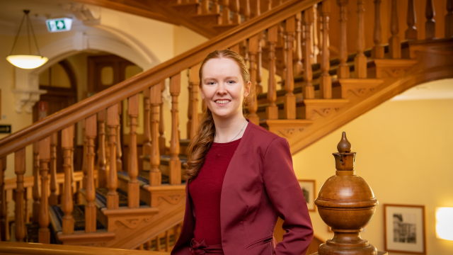 Girl with red hair and maroon suit with bow at waist and maroon top posing with golden wooden stairs in background and decorative wooden orb beside