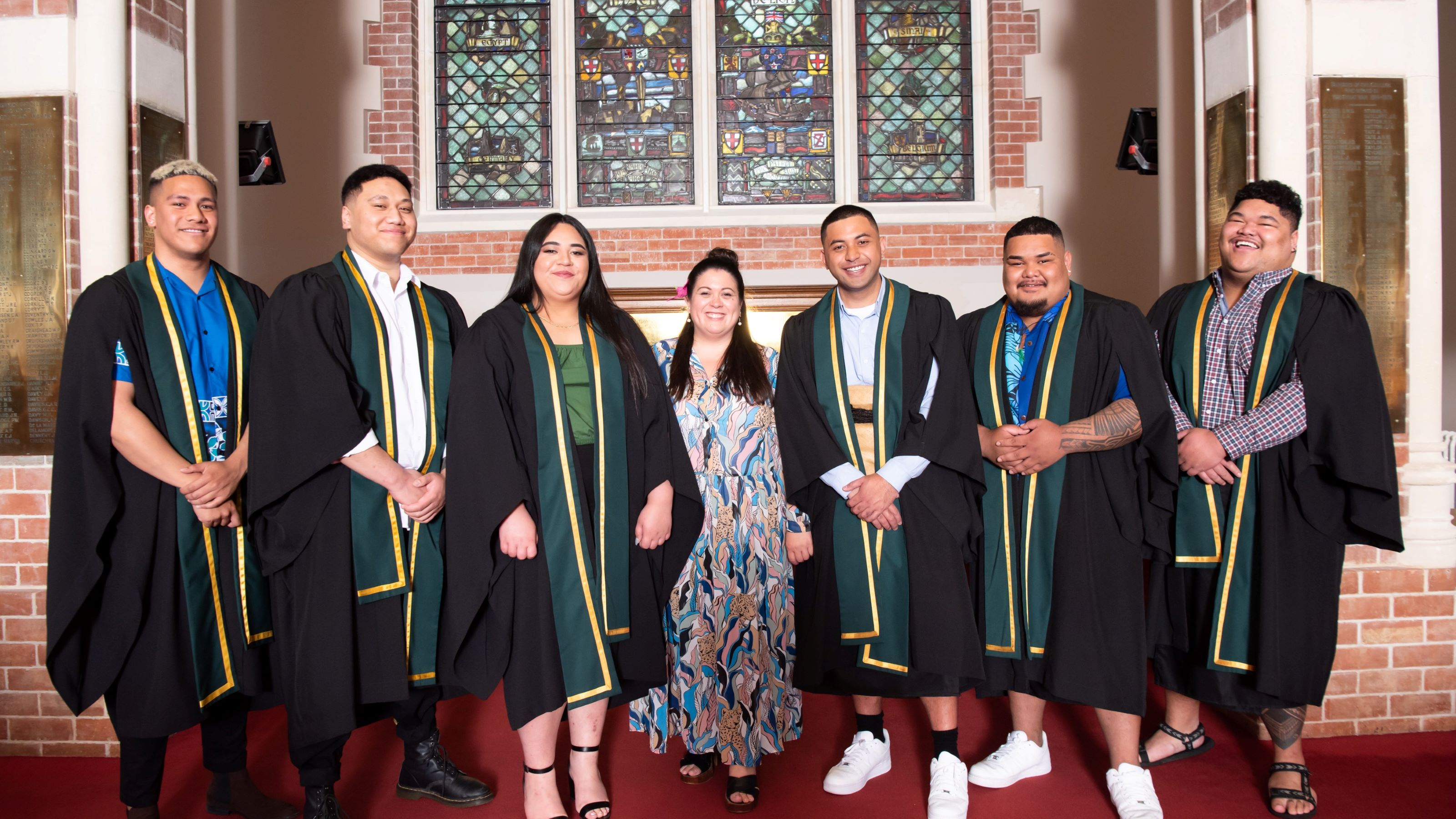 Pasifika students in academic dress (robe and sash) stand in front of a red brick wall with stained glass windows