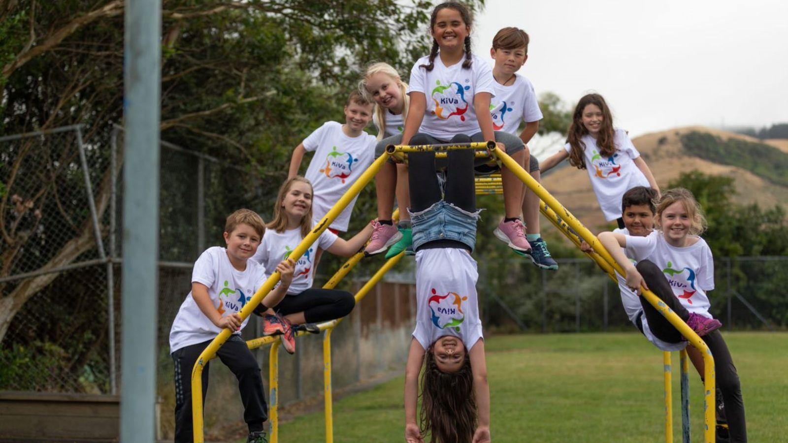 10 children posing on a yellow climbing frame, wearing white KiVa logo printed Tshirts