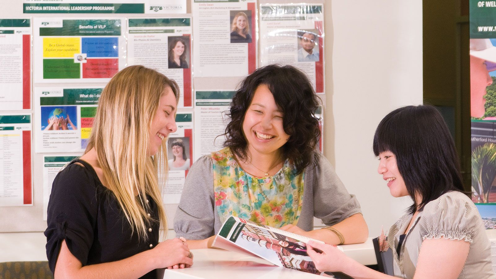 Two students, with an advisor smiling, while looking at a pamphlet.