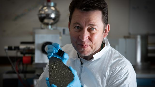 Dr Bruce Charlier holding a slice of the Allende meteorite