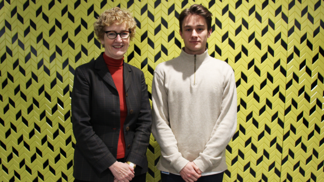 Professor Jane Bryson and Sam Dobbs stand together in front of yellow patterned wall.