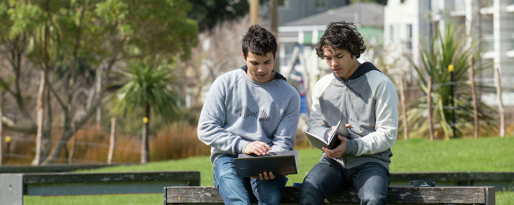 Two students working together during a discussion sitting on a bench in Waitangi park