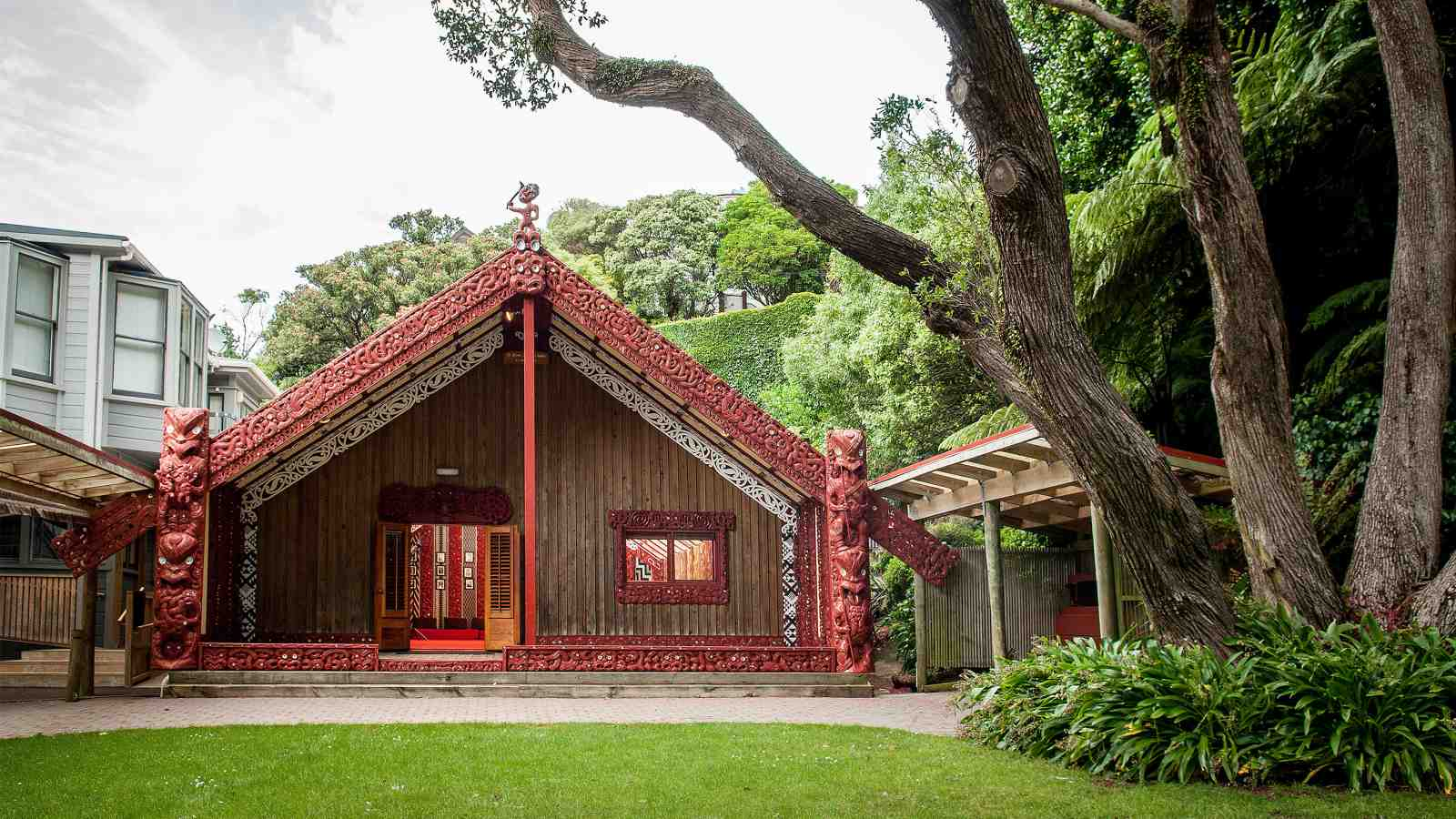 The entrance to the Marae taken from the outside across a green lawn.