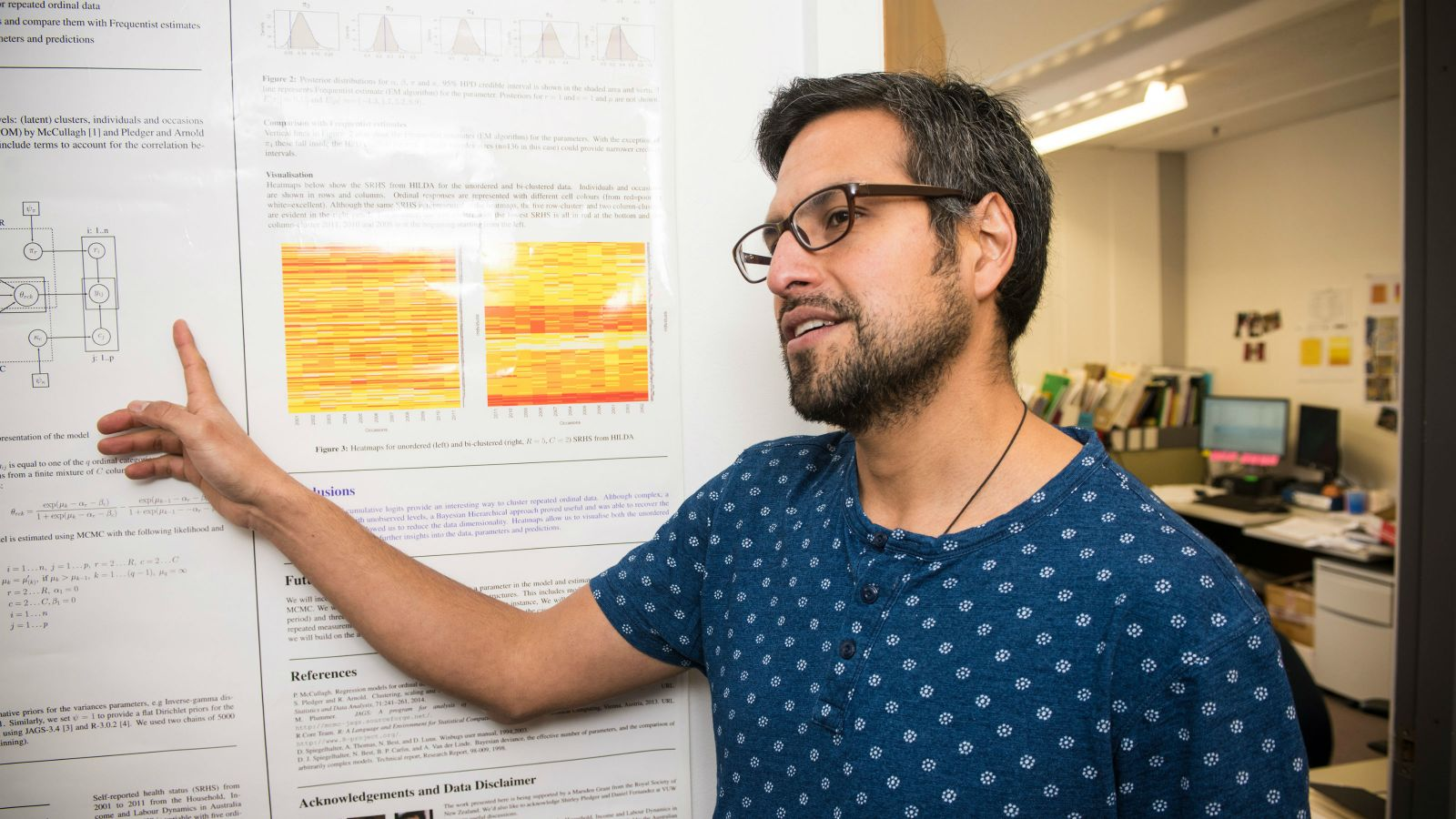 Roy Costilla points at his research poster