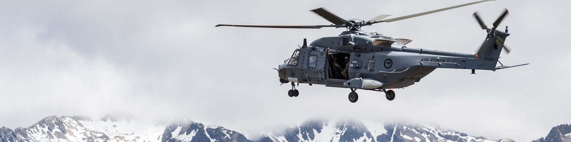 A large military helicpoter hovers in front of mountains under a cloudy sky