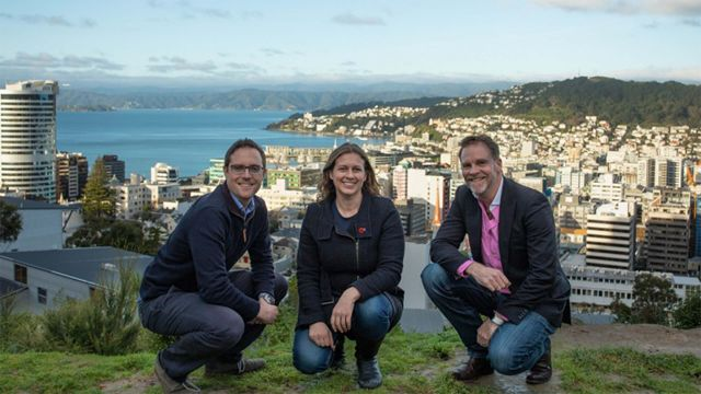 Two men and a woman kneel down for a group photo with Wellington central city behind them.