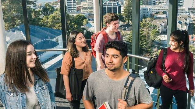 A group of students climb the stairwell in Rankine Brown, with a view of Wellington city out the windows behind them