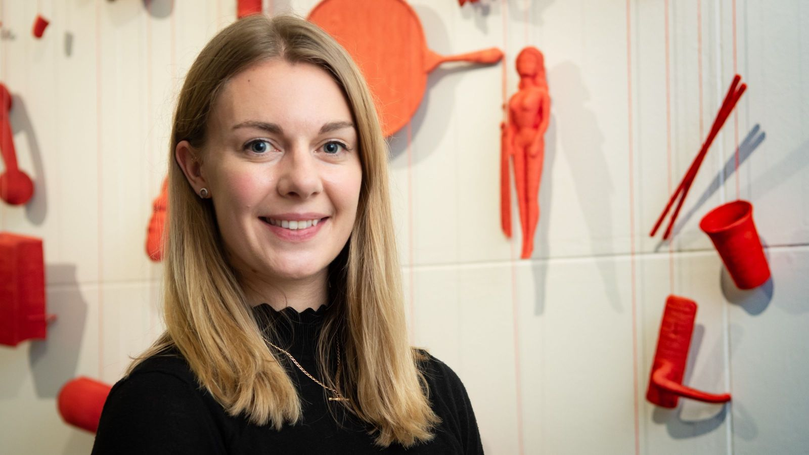 PhD Candidate Molly Fisher posing for a photo in front of a red art installation