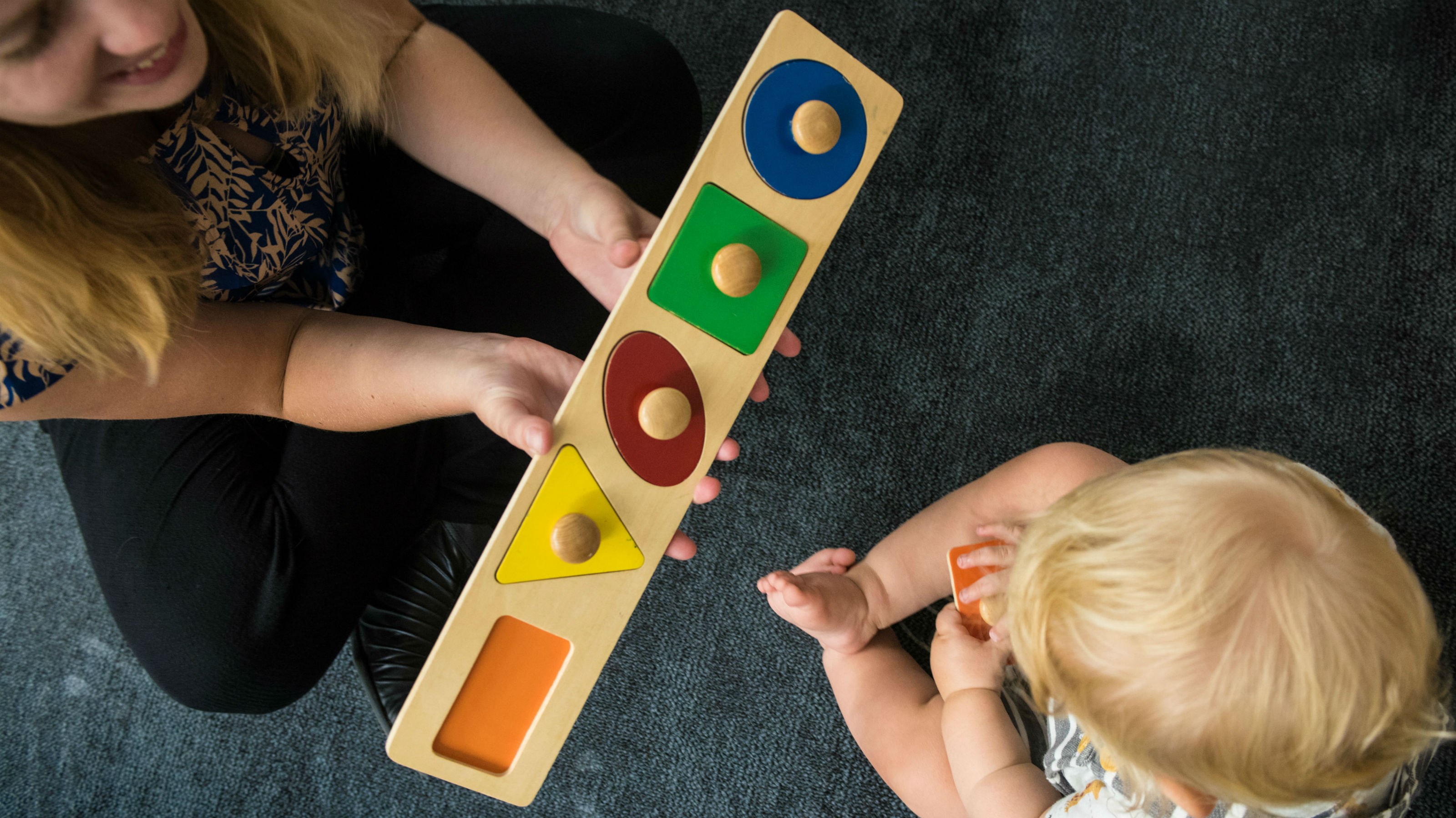 A view from above, a woman holds a wooden puzzle of four shapes, a young child holds an orange rectangular piece in his hand.