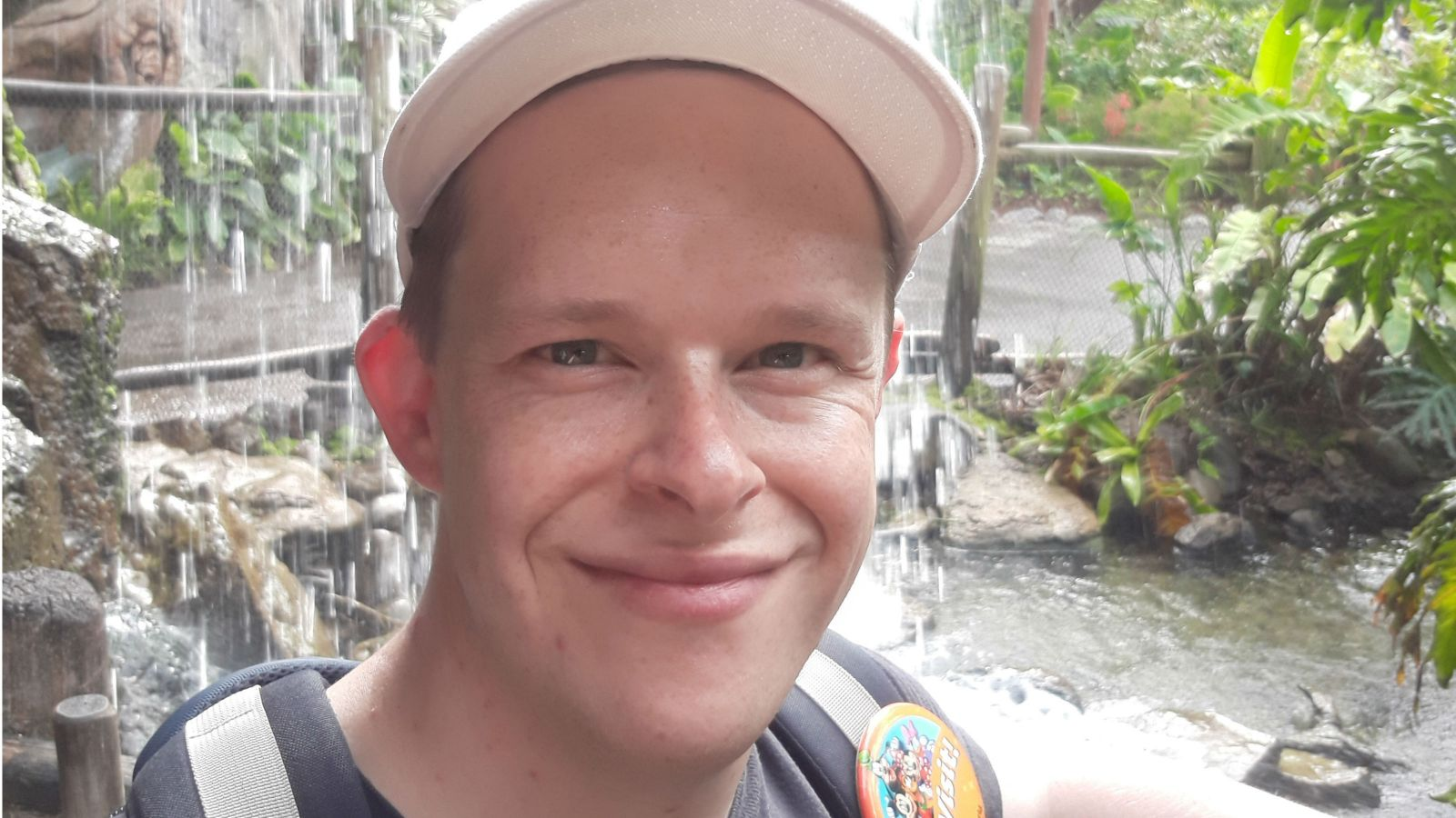 A close up of Lindsay, wearing a white cap, looking at the camera with a waterfall and plants behind him.