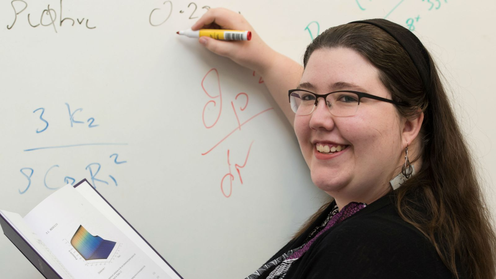 Emma Greenbank writes mathematical equations on a whiteboard with an book propped open.