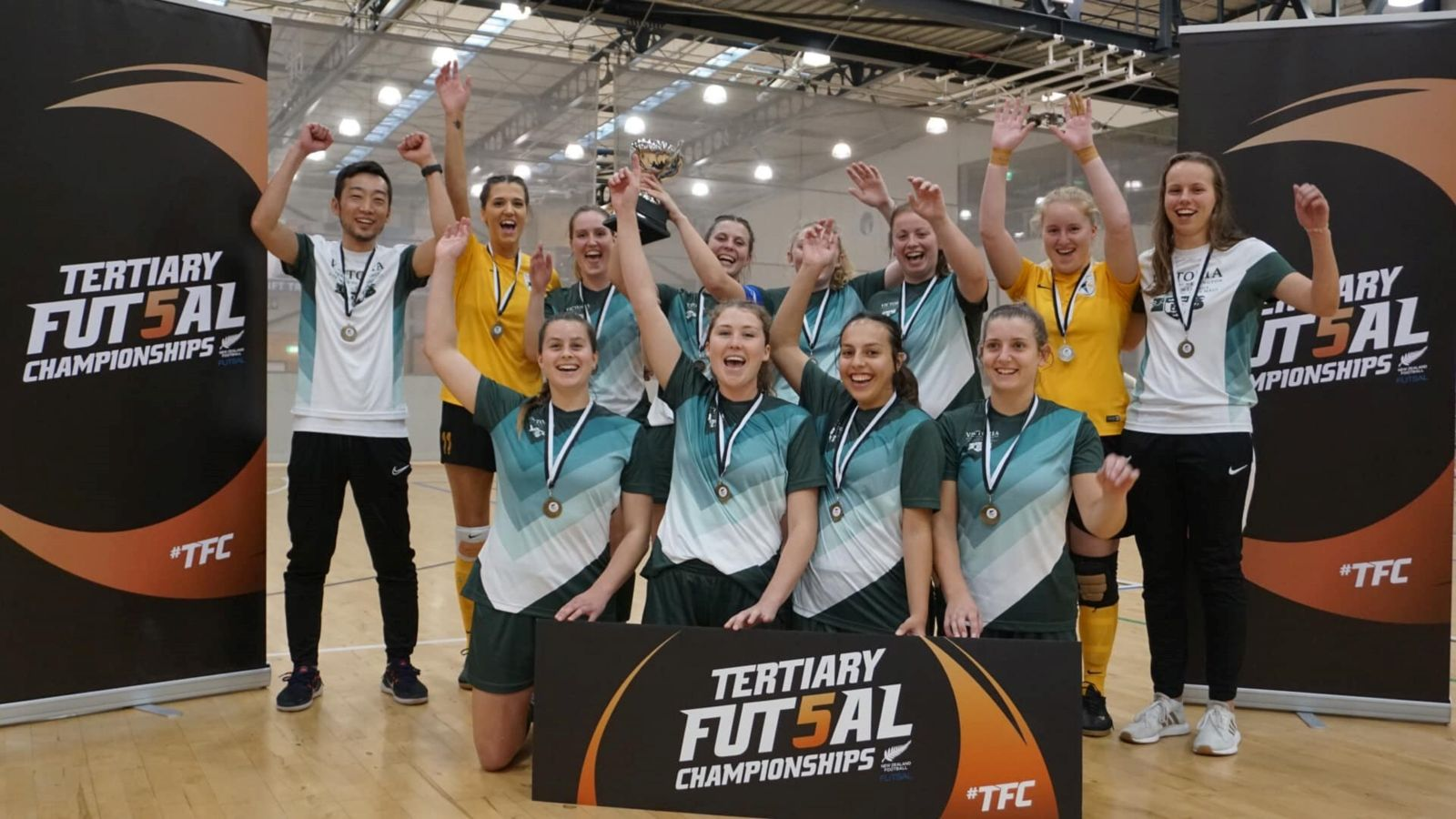 Victoria University of Wellington Women's Futsal team with medals, celebrating winning the 2019 tournament