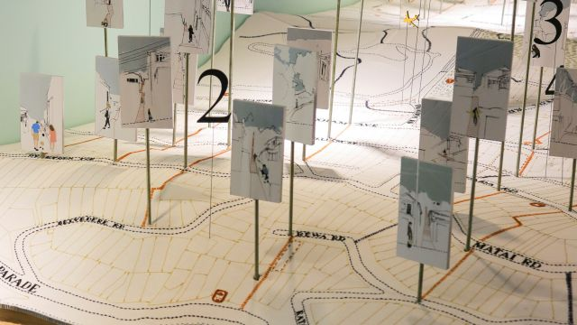 Embroidered map with architectural drawings of streets and houses added to it