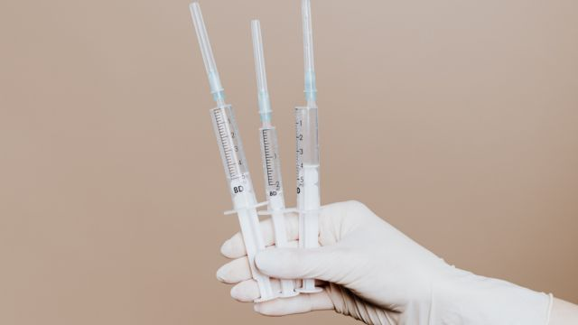 A hand in white glove holding three syringes.