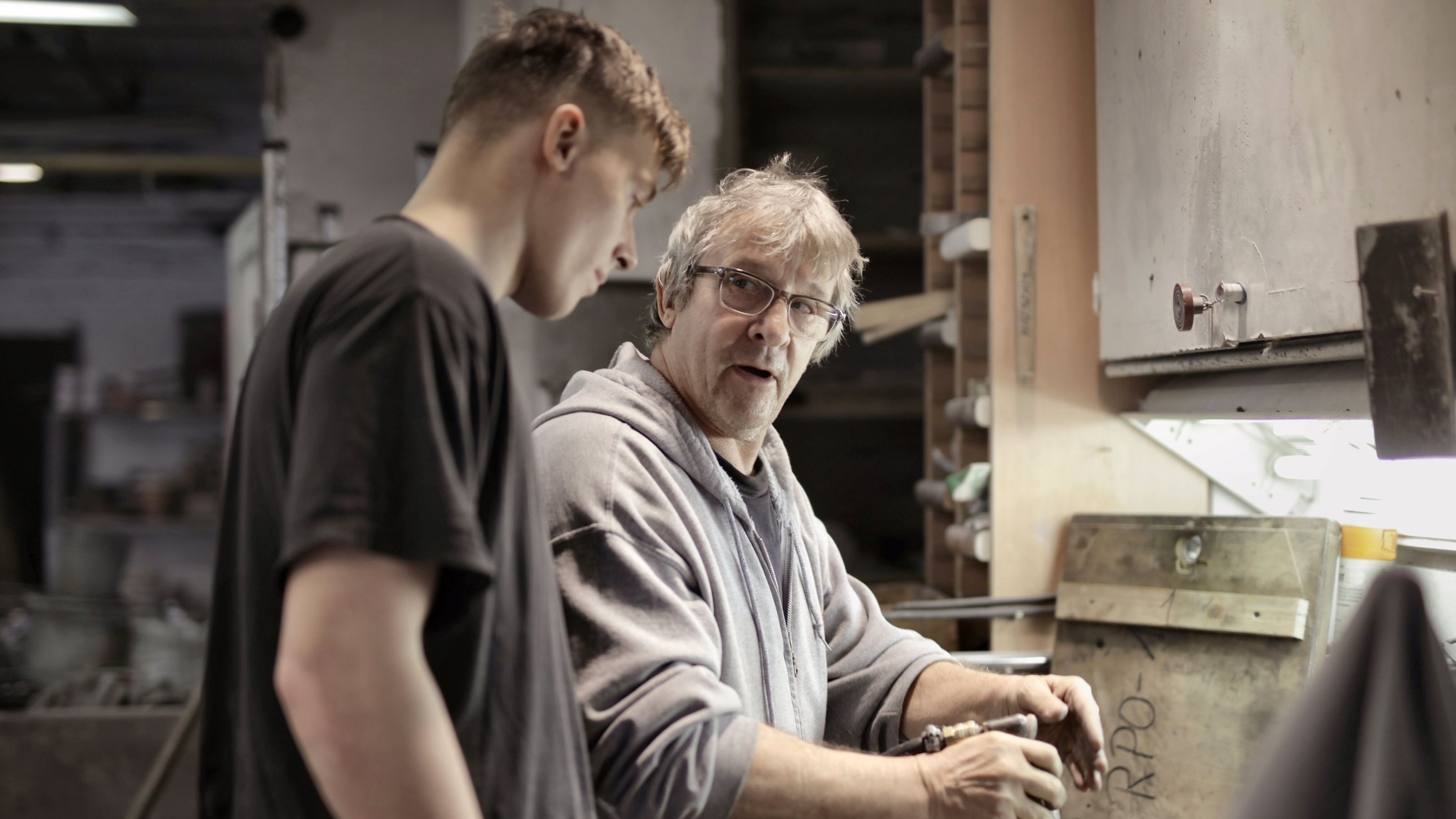 Two workers in discussion by pneumatic tool in workshop.