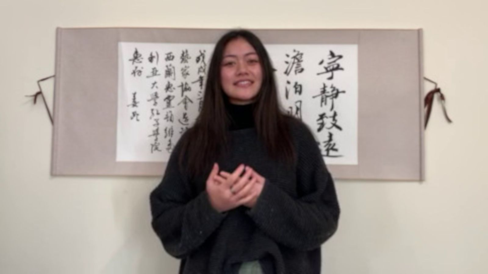 Monica Saili gives her winning speech in front of a piece of Chinese calligraphy