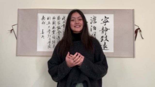 Monica Saili gives her winning speech in front of a piece of Chinese calligraphy.