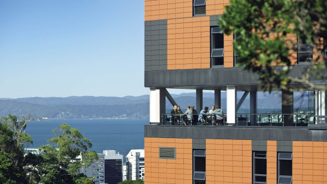 A group of students sitting in the dining room of Te Puni Village hall of residence which overlooks Wellington harbour.