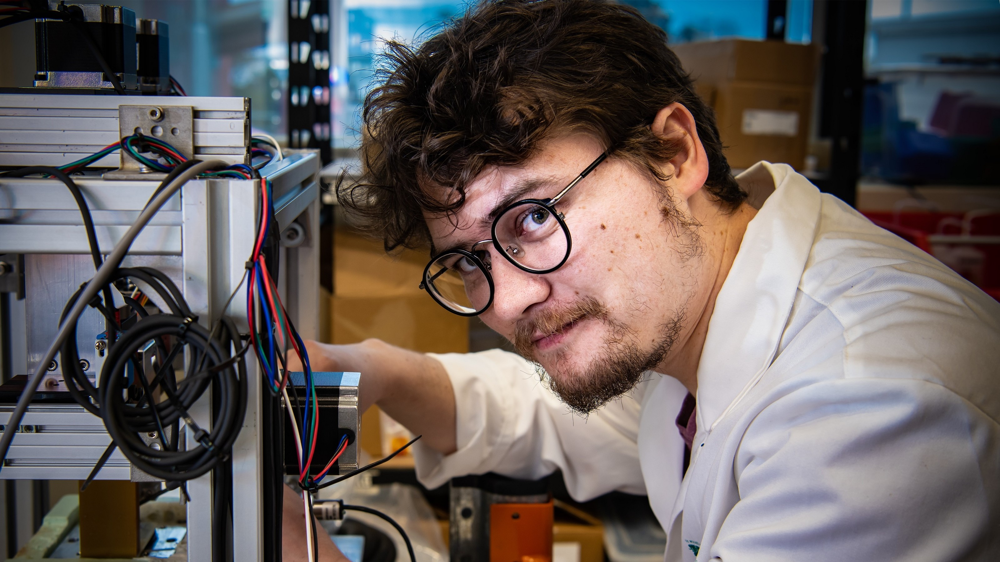 Male student with round glasses in labcoat, at Robinson Research Institute.