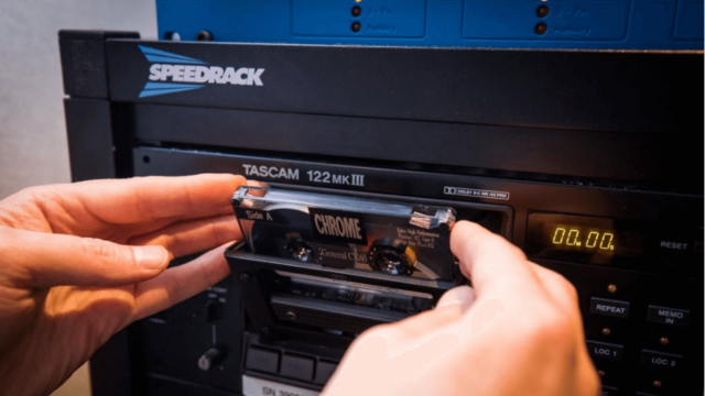 Two hands inserting a tape in a cassette player.