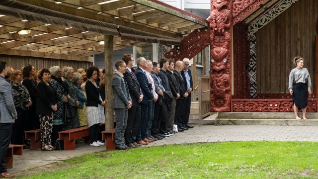 Guests at the blessing ceremony stand outside the marae during the powhiri