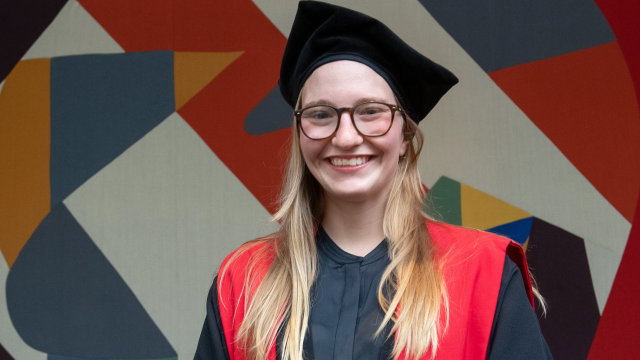 Girl with long blonde hair grinning, wearing a tricorn hat and doctoral robes