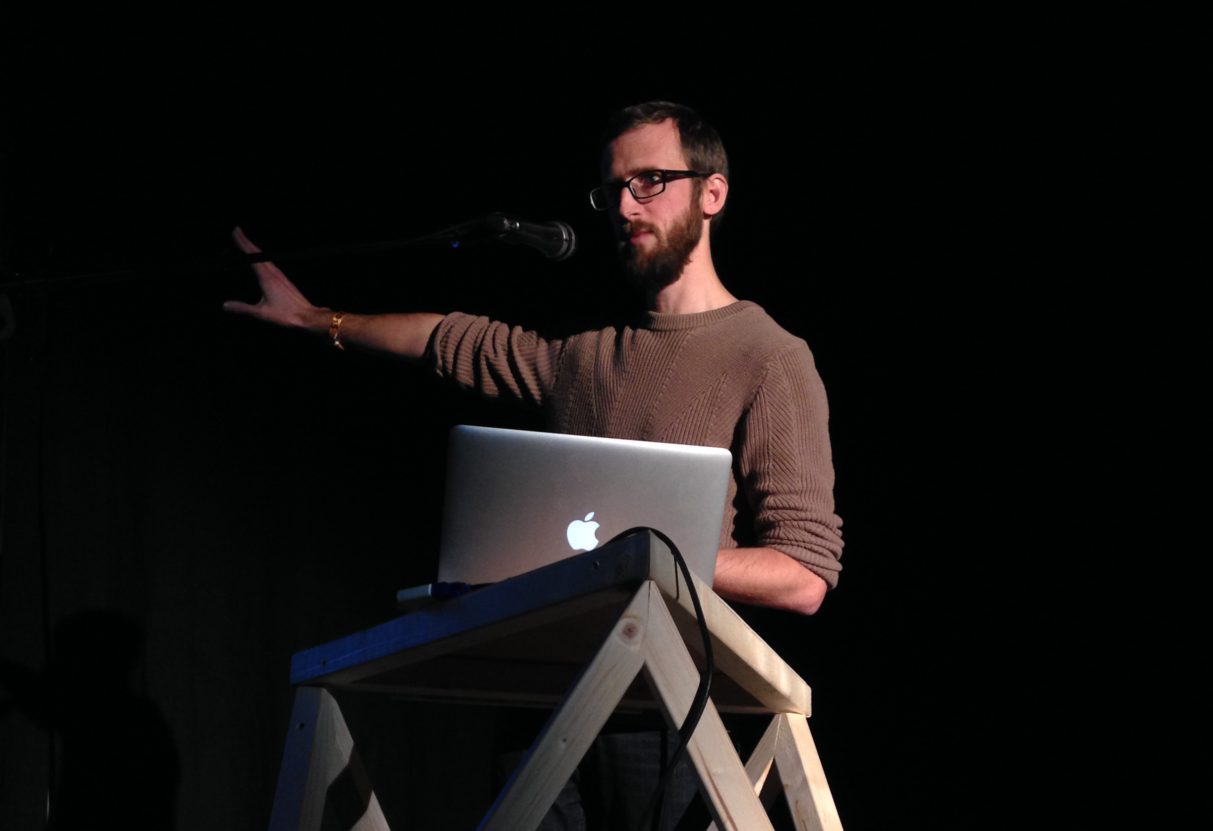 Pippin Barr presenting on stage at a conference.