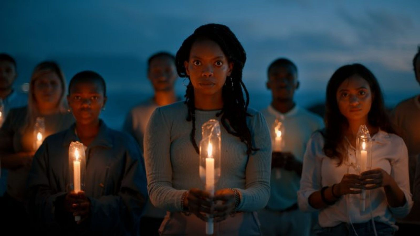 people in twilight holding candles