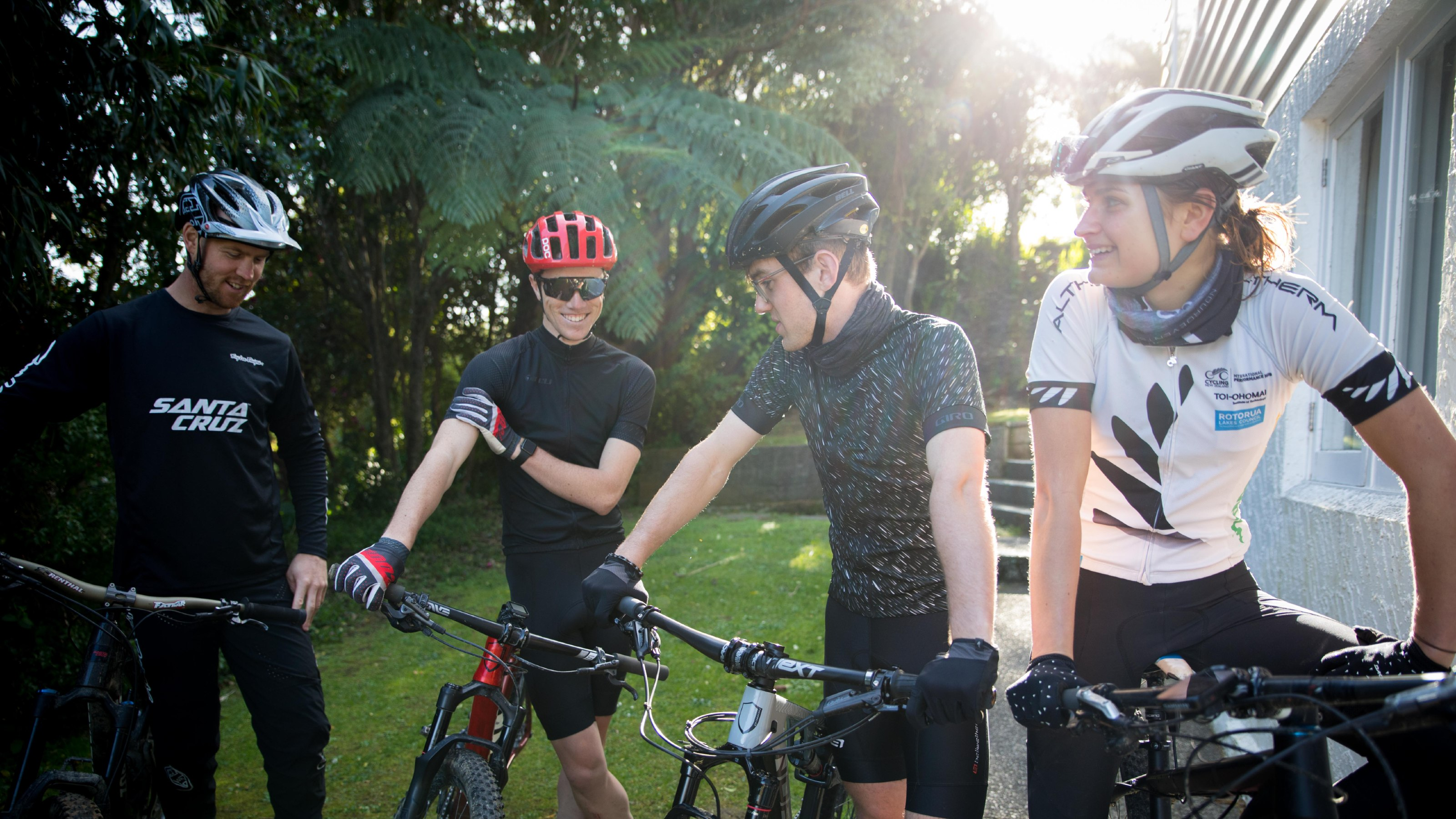 Four students with their mountain bikes, wearing helmets and cycling gear.