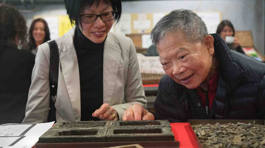 Winnie Chan and Laywood Chan look at decorative borders used for invitations.