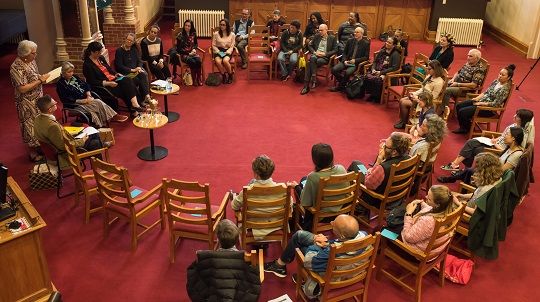 The group of 30 guests from above sitting in a circle as if around a campfire.