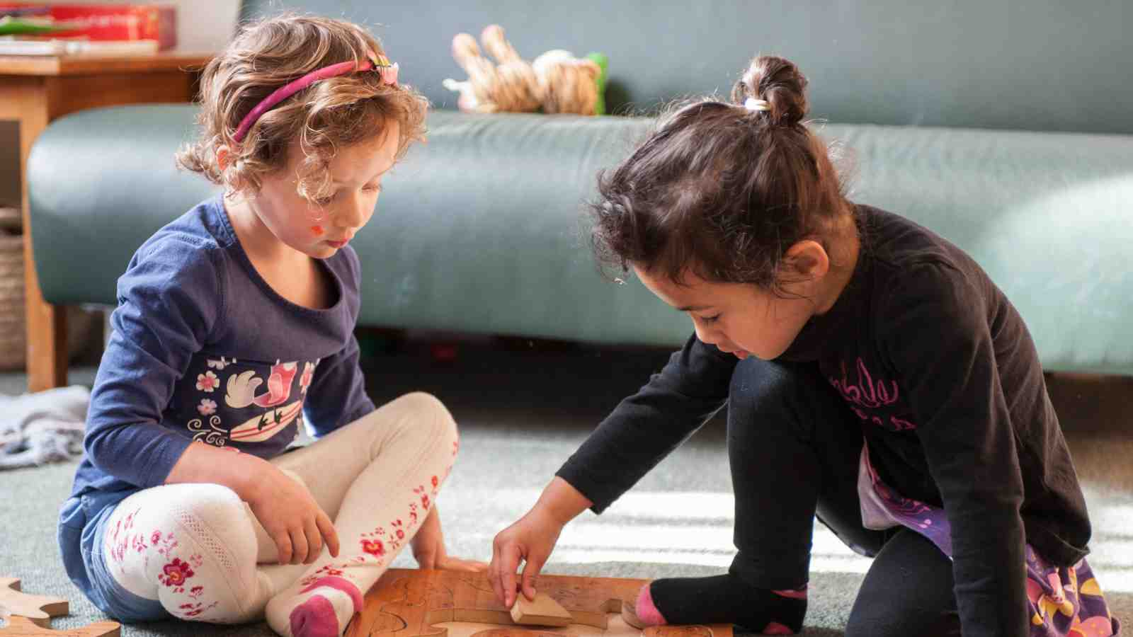 20 Hours Eerly Childhood Education – Two young girls play with a wooden puzzle together.