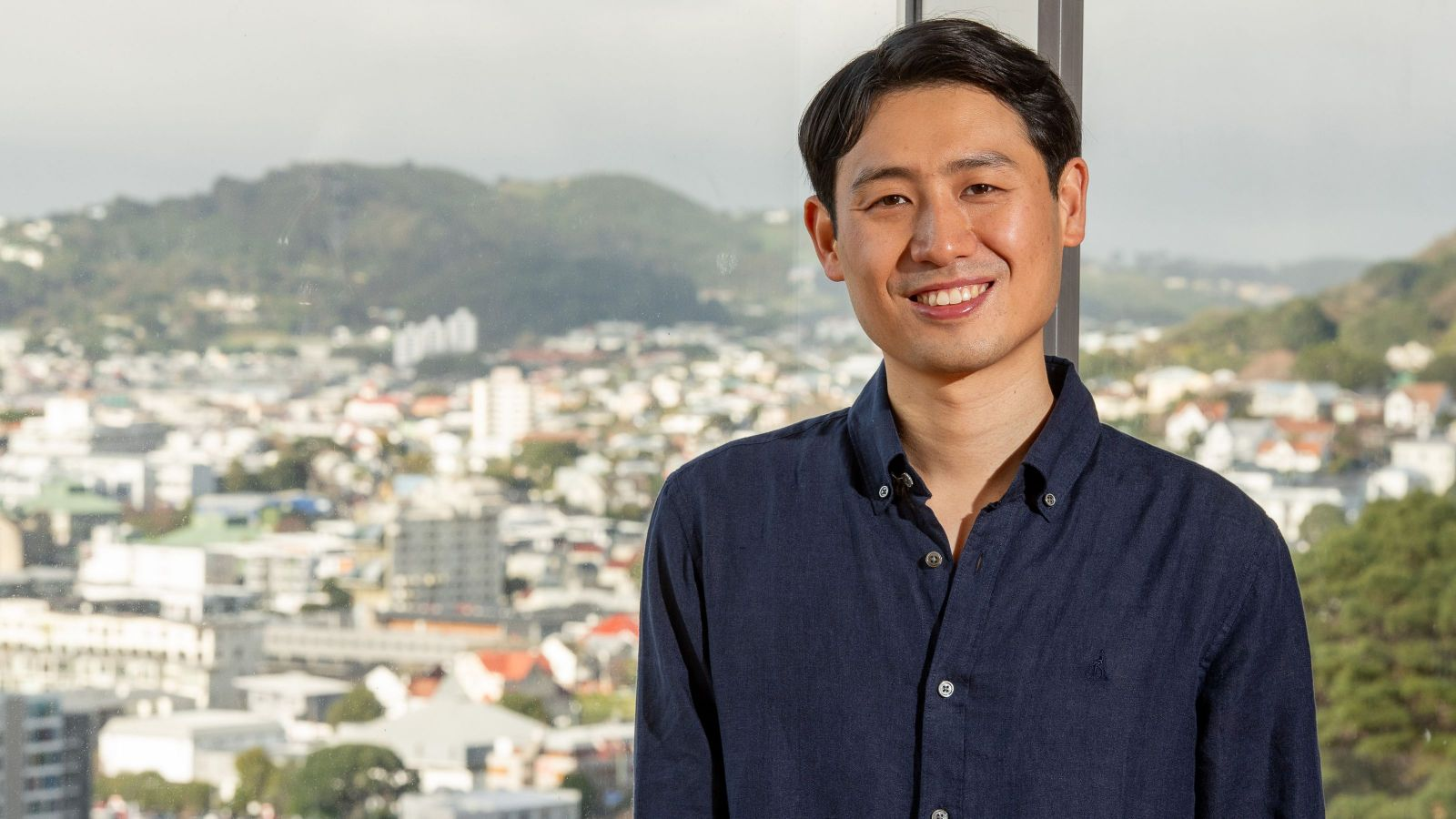 PhD Candidate In Kuk Kim standing for a photo in front of a window with Wellington City in background