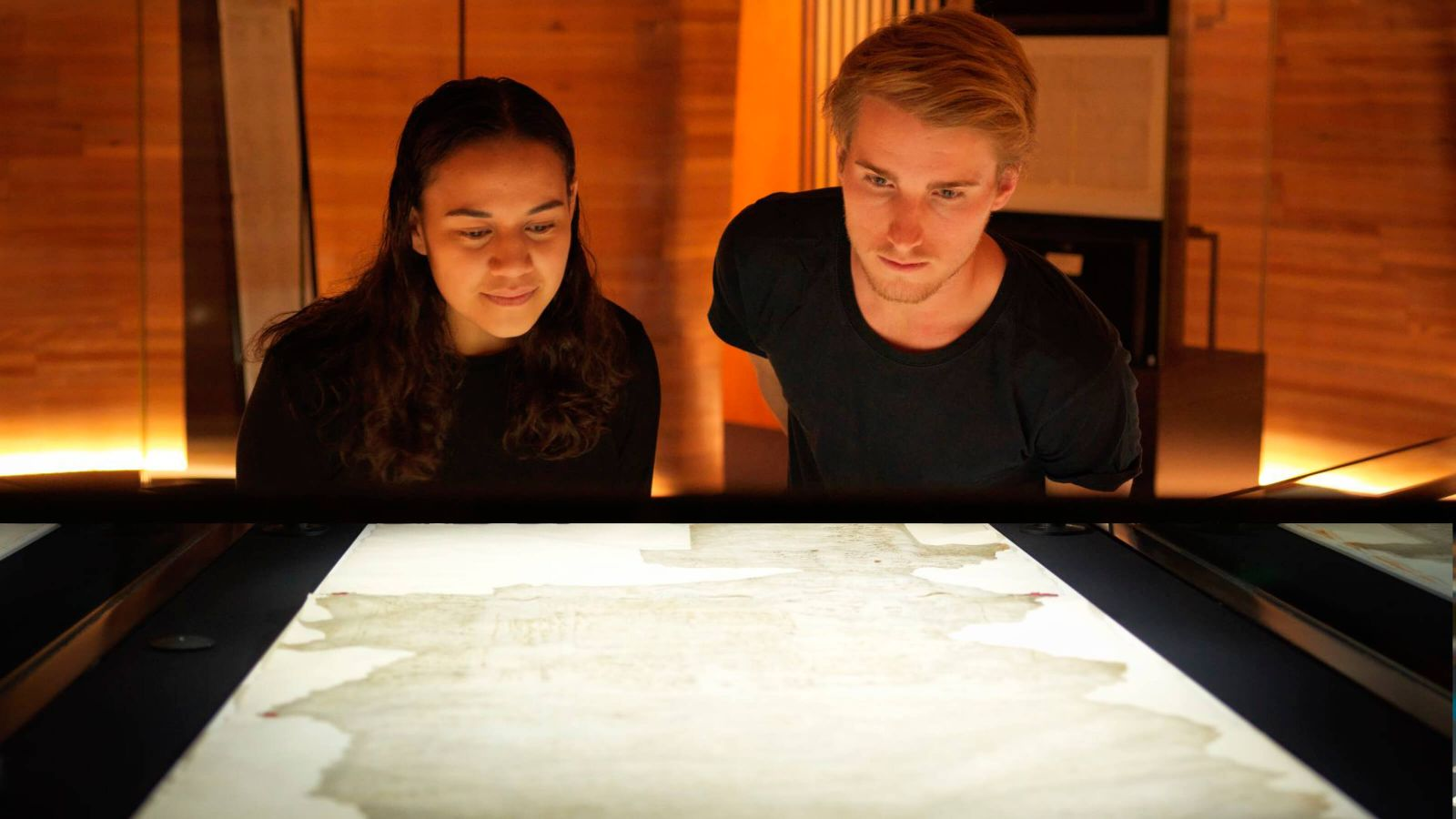 Two students look down over a backlight surface the illuminates an old map.