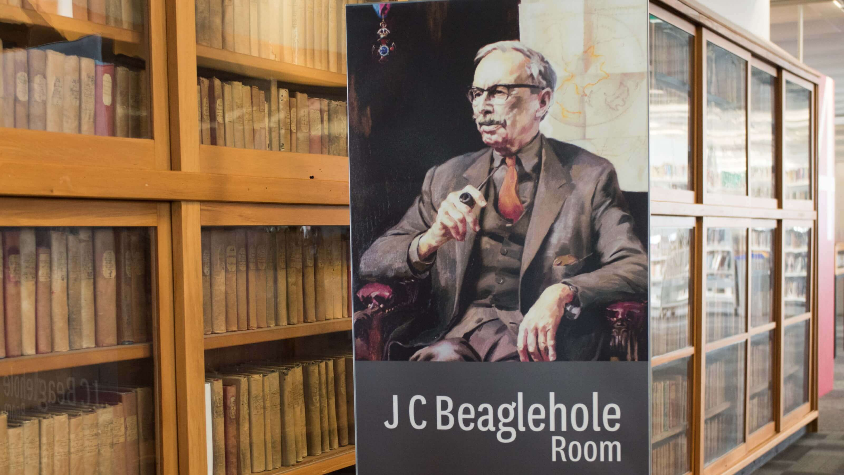 photo of a JC Beaglehole illustrated portrait attached to the end of a bookshelf.