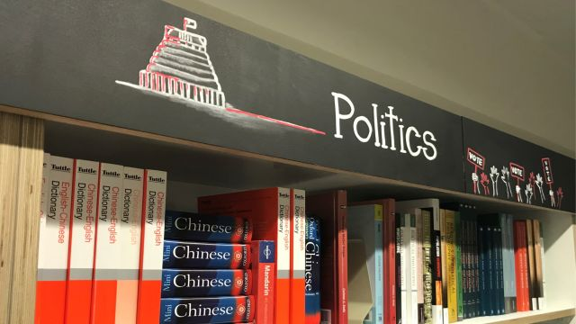 Bookshelf with Chinese—English dictionaries and various other books under a sign that says 'Politics'.