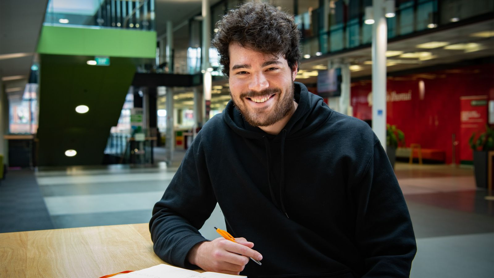 Anthony Charsley smiling while taking some notes