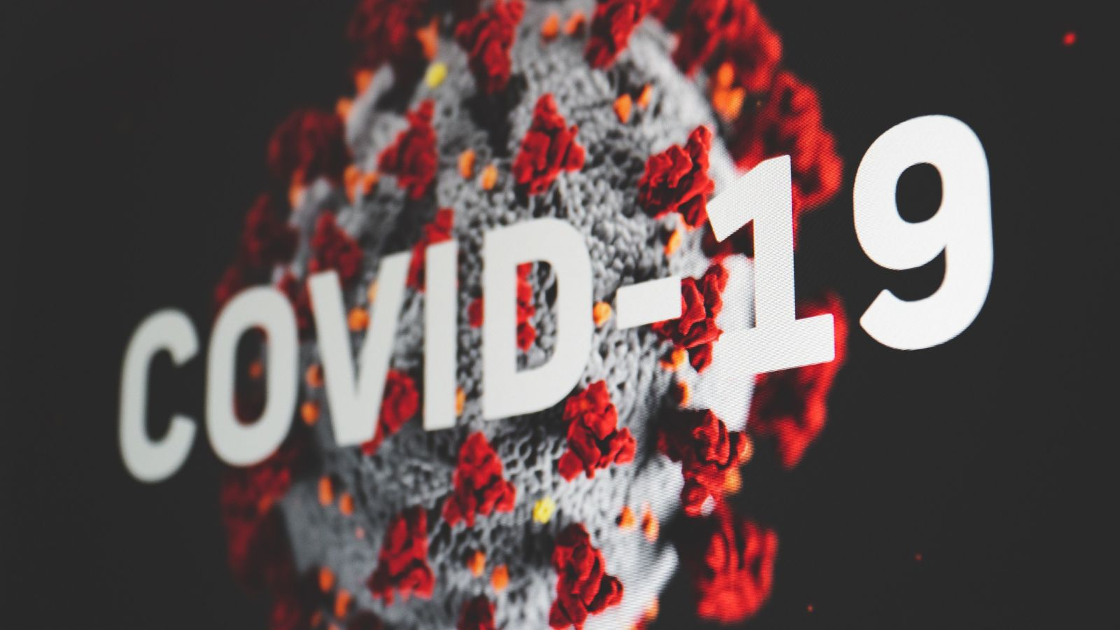 Picture of a virus with text 'COVID-19' in front