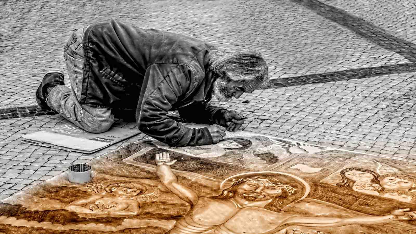 graffiti artist finishing mural on pavement