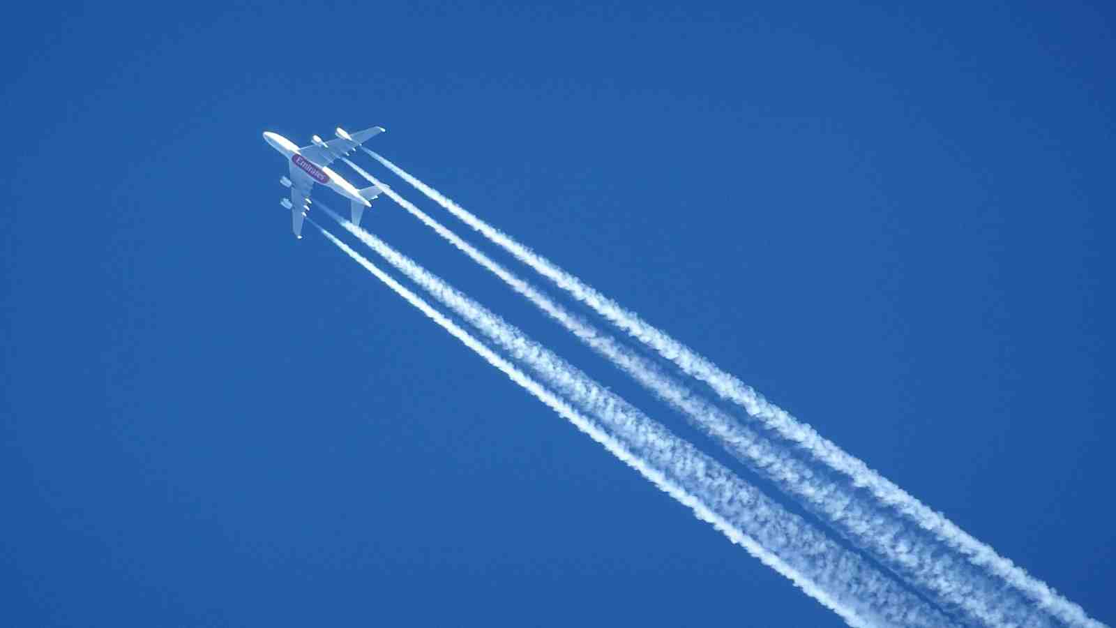 image of flying planes leaving emissions across the sky