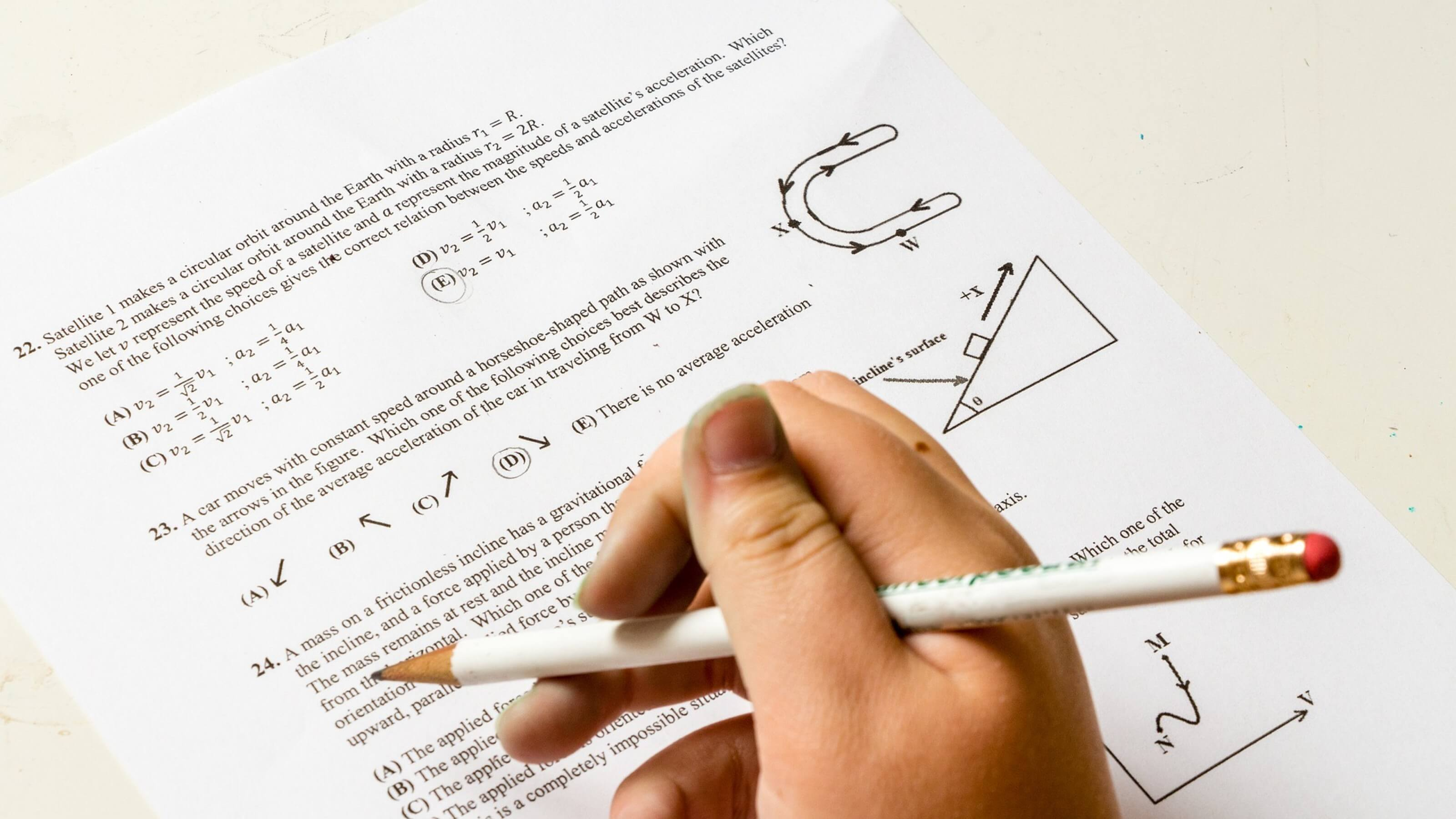 A close up of a hand holding a pencil filling in an exam paper.