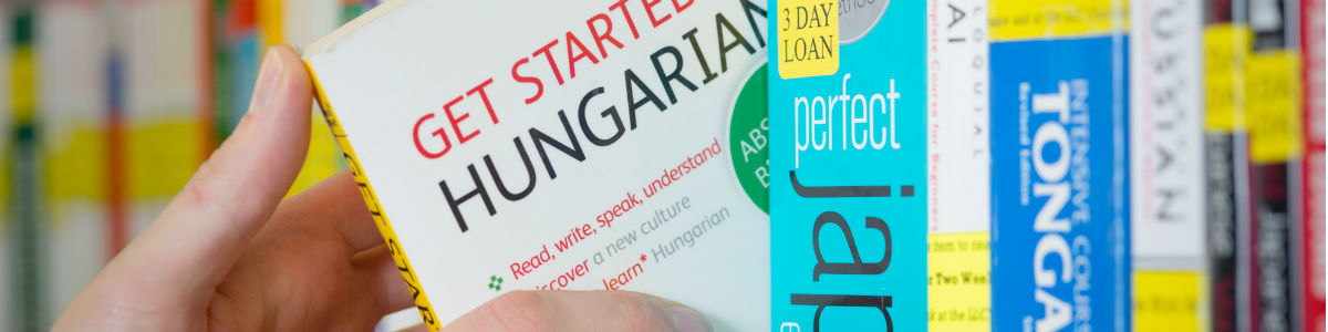 """Banner image – a hand pulls a book off of a shelf the reads """"Get started Hungarian""""."""