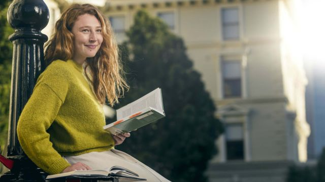 Law and Science student, Melissa Harward, is sitting and reading a book in front of the Old Government Buildings on Lambton Quay, Wellington.