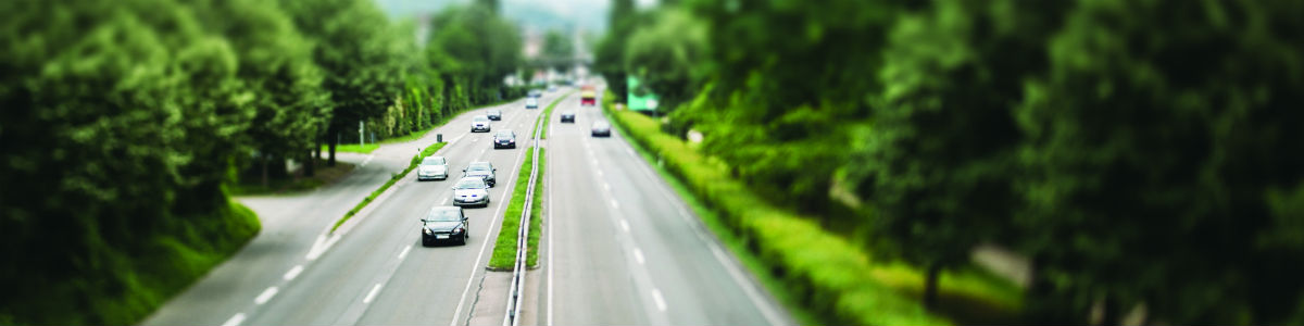 Banner image – cars driving on a highway in a wooded area.