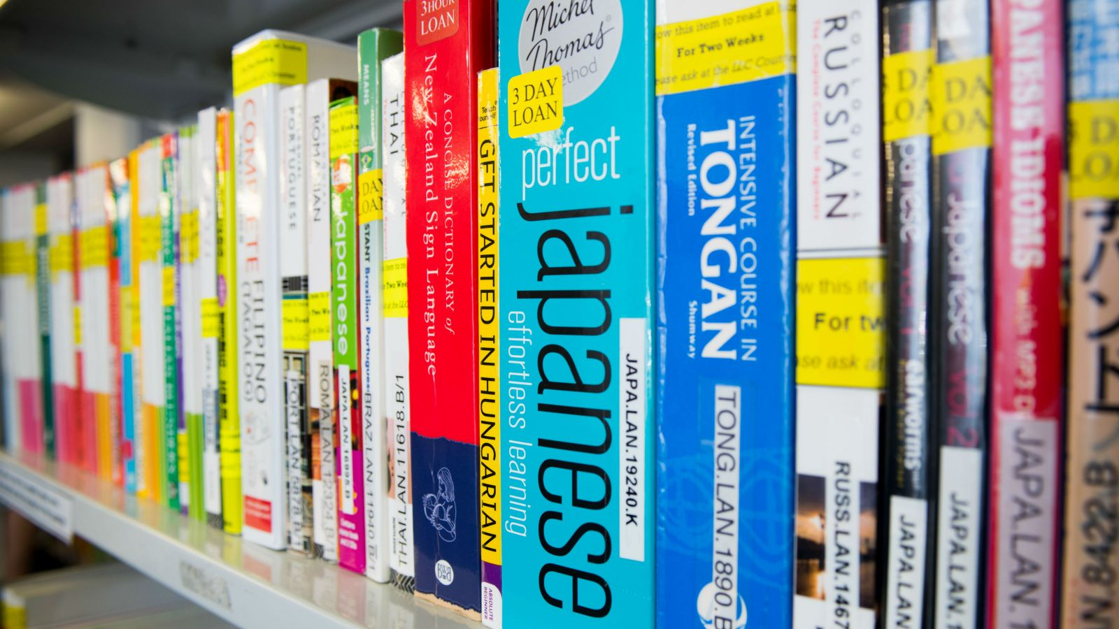 The spines of many language books on a shelf.