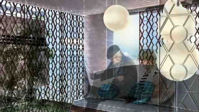 Computer generated image showing two elderly people sitting in their living room reading the paper, in the back and foreground mashrabiya, lattice-like screens to enhance privacy, can be seen.