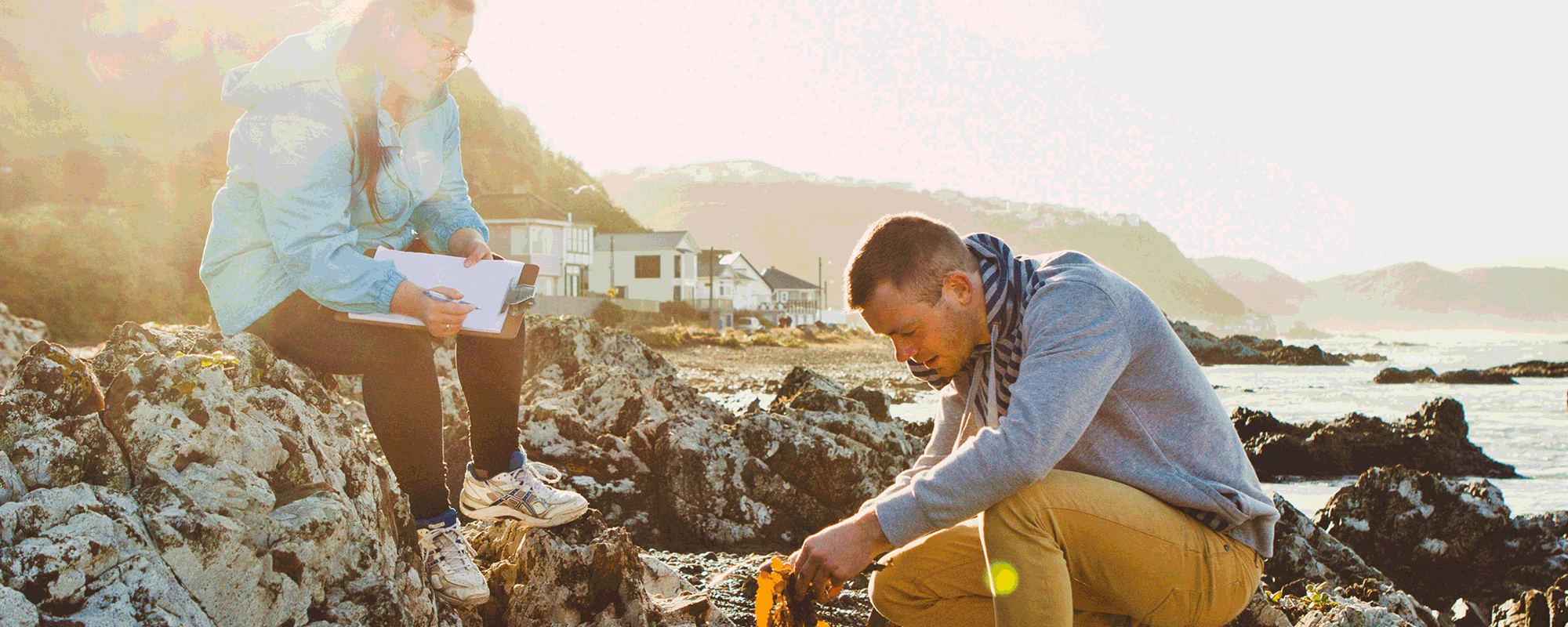 Two research students work are searching through coastal rocks holding a piece of algae.
